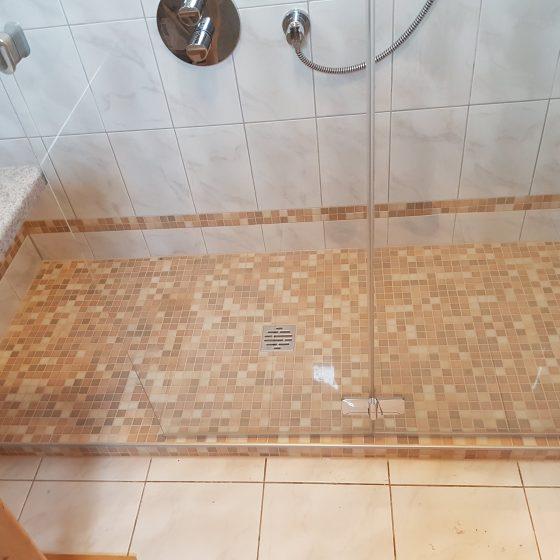 fast bodenenbe Dusche mit kleiner Stufe, extrabreitem Eingang und rutschhemmender Mosaik-Verfliesung in freundlichen Brauntönen