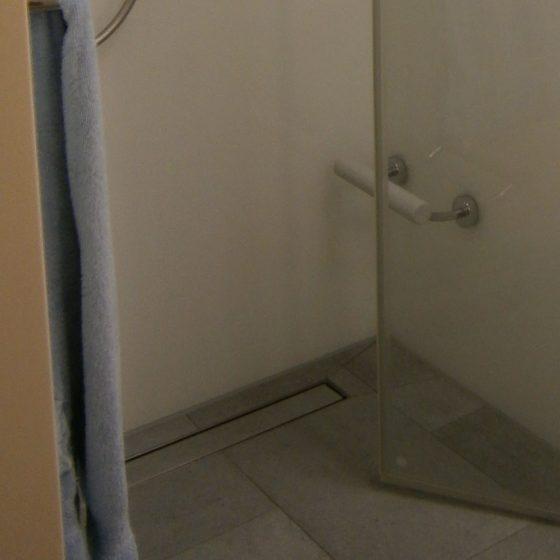 Fußstuetze in Dusche mit gefliestem Boden und gefliester Duschrinne