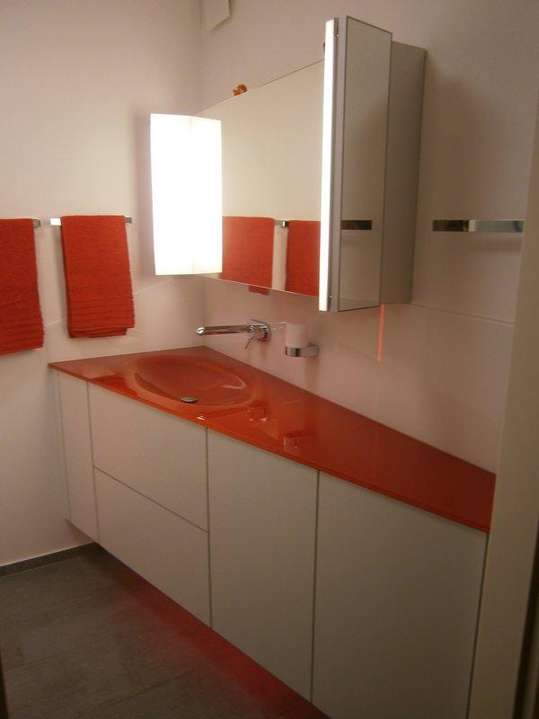 Waschtischloesung gezogener Glaswaschtisch in Orange schraeg geschnittene Badmoeblage in Weiss Spiegelschrank mit klappbaren Seitenfluegeln