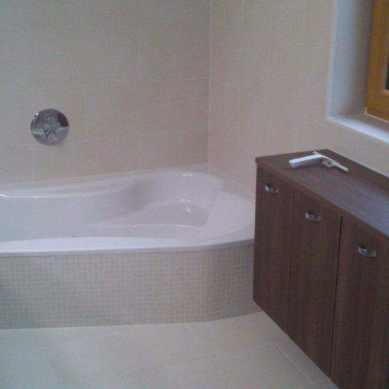 großzügige Eckbadewanne mit angeformten Sitzplatz