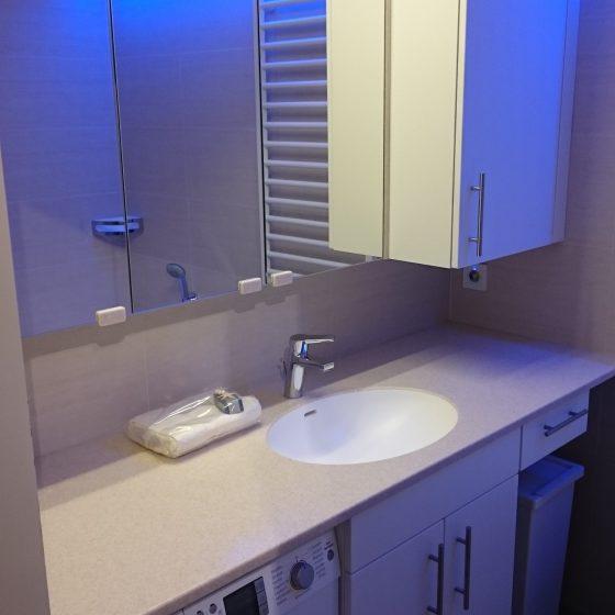 Waschtisch eingelassen in maßangefertigte Staron-Platte mit Spiegel-, Ober- und Unterschrank