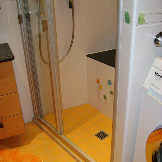 Dusche mit Schiebtür und gemauertem Sitzplatz mit fröhlicher gelber Bodenverfliesung und Steuerl-Wandfliesen mit Janosch-Fröschen