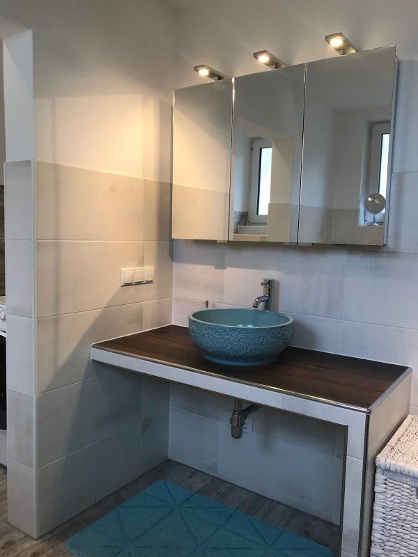türkisblaue Aufsatz-Waschschüssel auf gemauerter Waschtisch-Bank mit Platz für Roll-Container darunter