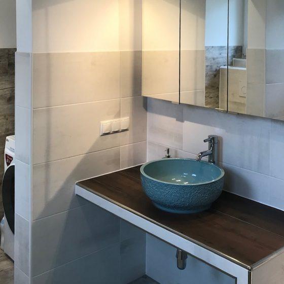 türkise Waschschüssel auf einer verfliesten Waschtisch-Mauerbank, darüber ein dreitüriger Spiegelschrank