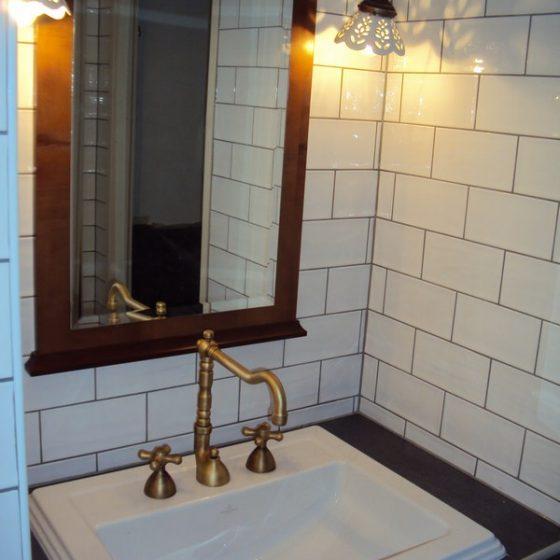 Handwaschbecken mit bronzierten Armaturen einem Spiegel mit Holzrahmen im Retro-Stil