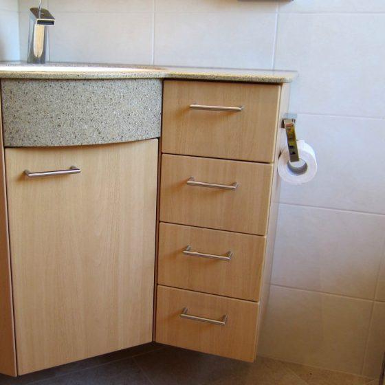 Ein Eckwaschtischverbau mit einer Corianplatte und viel Stauraum im Unterbau dient gleichzeitig als Platz um den WC-Rollenhalter für das daneben situierte WC zu befestigen