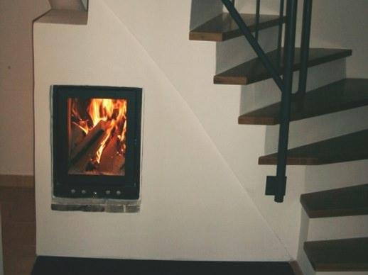knisterndes Feuer hinter einer Kamin-Sichtscheibe im Wohnzimmer