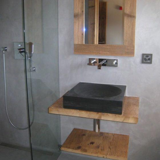 Neuheiten und Trends: Bad in Beton Cire mit Waschtischensensemble und Spiegel aus Holz sowie dunklem eckigen Aufsatzwaschbecken