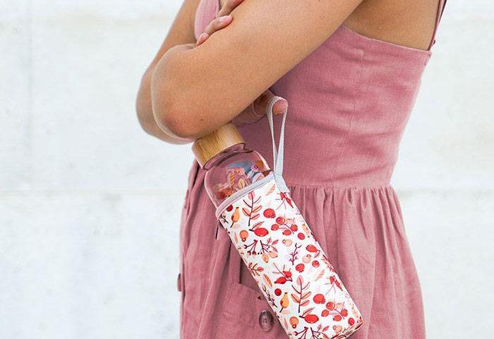 Frau lässt Waterdrop-Flasche im Thermosleeve an der Halteschlaufe baumeln