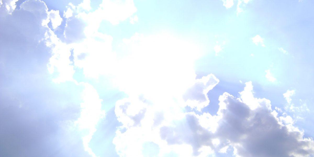 Blick hinauf auf hell leuchtende Wolken am Himmel