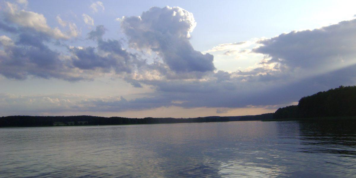 Abendstimmung mitten auf einem See mit ruhigem Wasser in dem sich die Wolken spiegeln