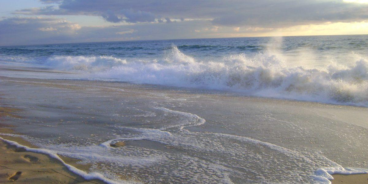 Sandstrand mit Wellen die schäumend auf- und zurücklaufen und sich am Ufer brechen