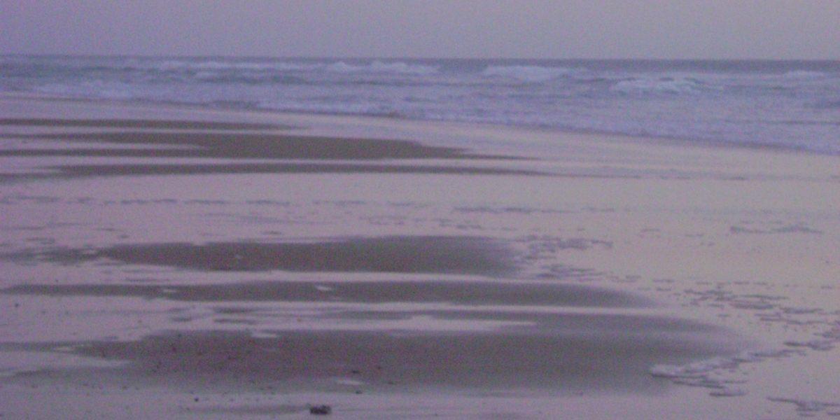 Abenstimmung die Sand und Uferwellen in Rosa-Lila-Stimmung taucht