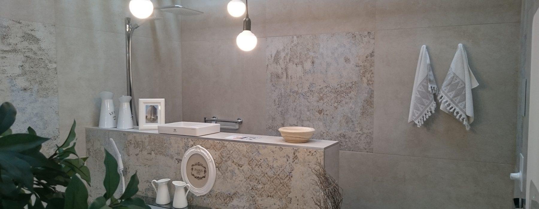 Bad mit Wanne und Dusche hinter halbhohem Raumteiler verfliest mit Großformat-Fliesen