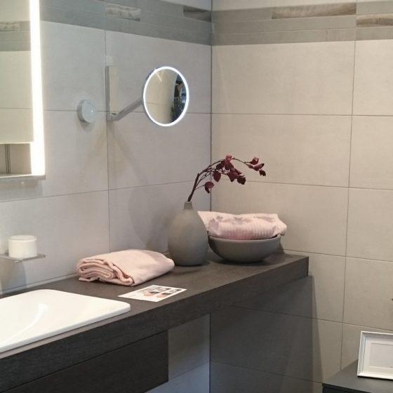 Wohlfühlatmosphäre in einem grauen Bad durch Handtücher und Deko in Rosa