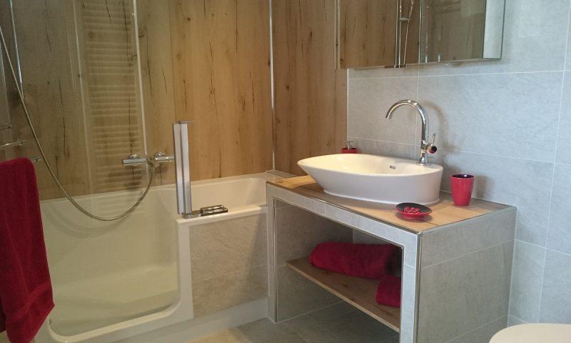 Bad mit Artweger Twinline 2, Wandpaneelen in Holzoptik, Aufsatzwaschbecken auf gefliester Mauerbank mit offenem Regalfach