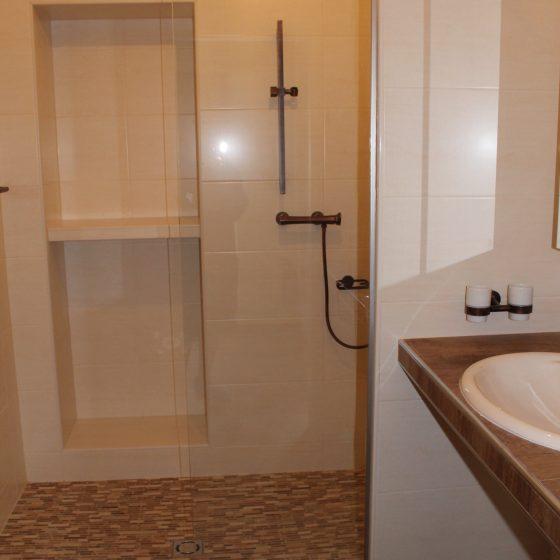 bodenebene offene Walk-in-Duschlösung mit Fixglas, gemauerter Duschnische für Duschutensilien und Sitzplatz