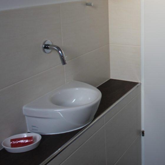 kleines Handwaschbecken im WC auf der Mauerbank montiert so dass sich die Tür gut öffnen lässt